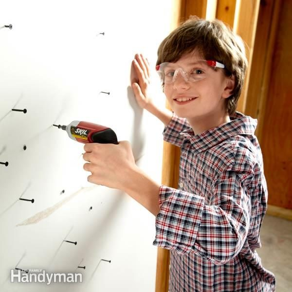 young boy smiles as he uses a drill on screws