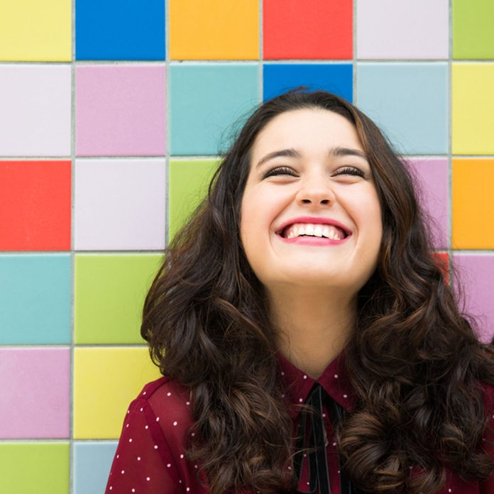 Happy girl laughing against a colorful tiles background. Concept of joy; Shutterstock ID 332500766