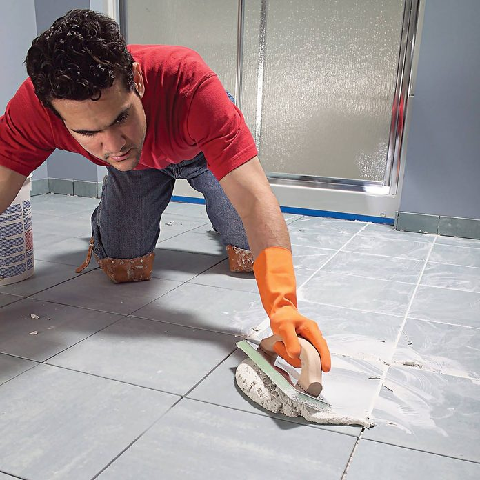 Man grouts tile in a bathroom