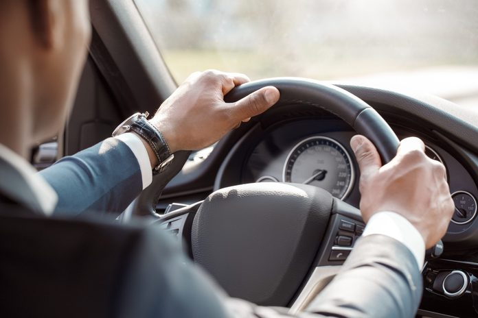 Young black businessman driver wearing expensive watch sitting inside the car driving holding steering wheel close-up back view