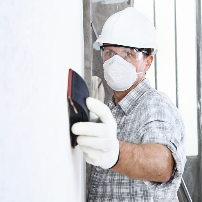 Man wearing a mask and sanding a wall