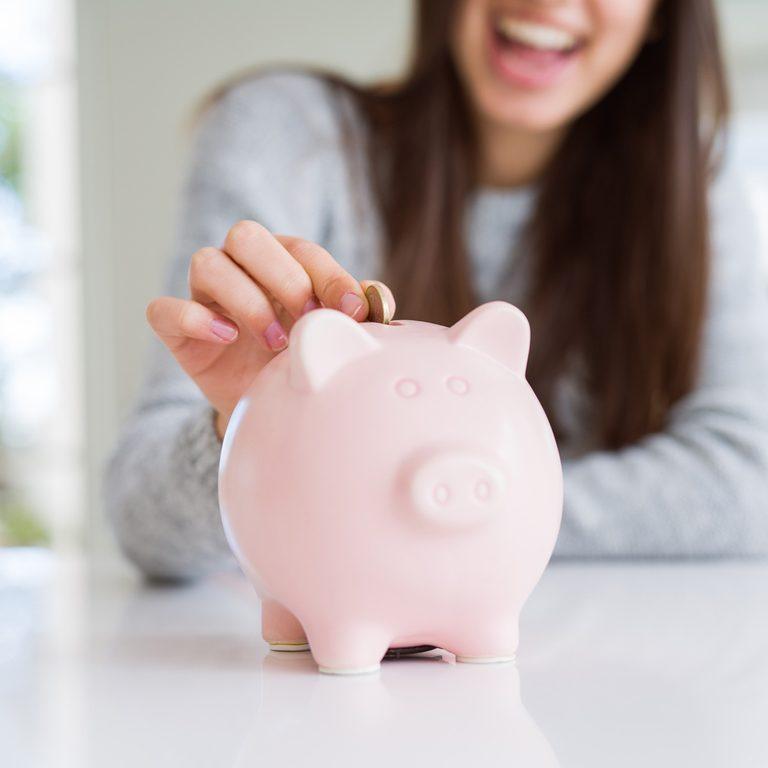 Woman putting money in a piggy bank