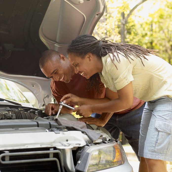 Couple fixing their car