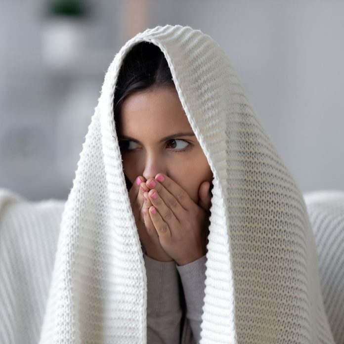 Woman sitting under a blanket, covering her mouth
