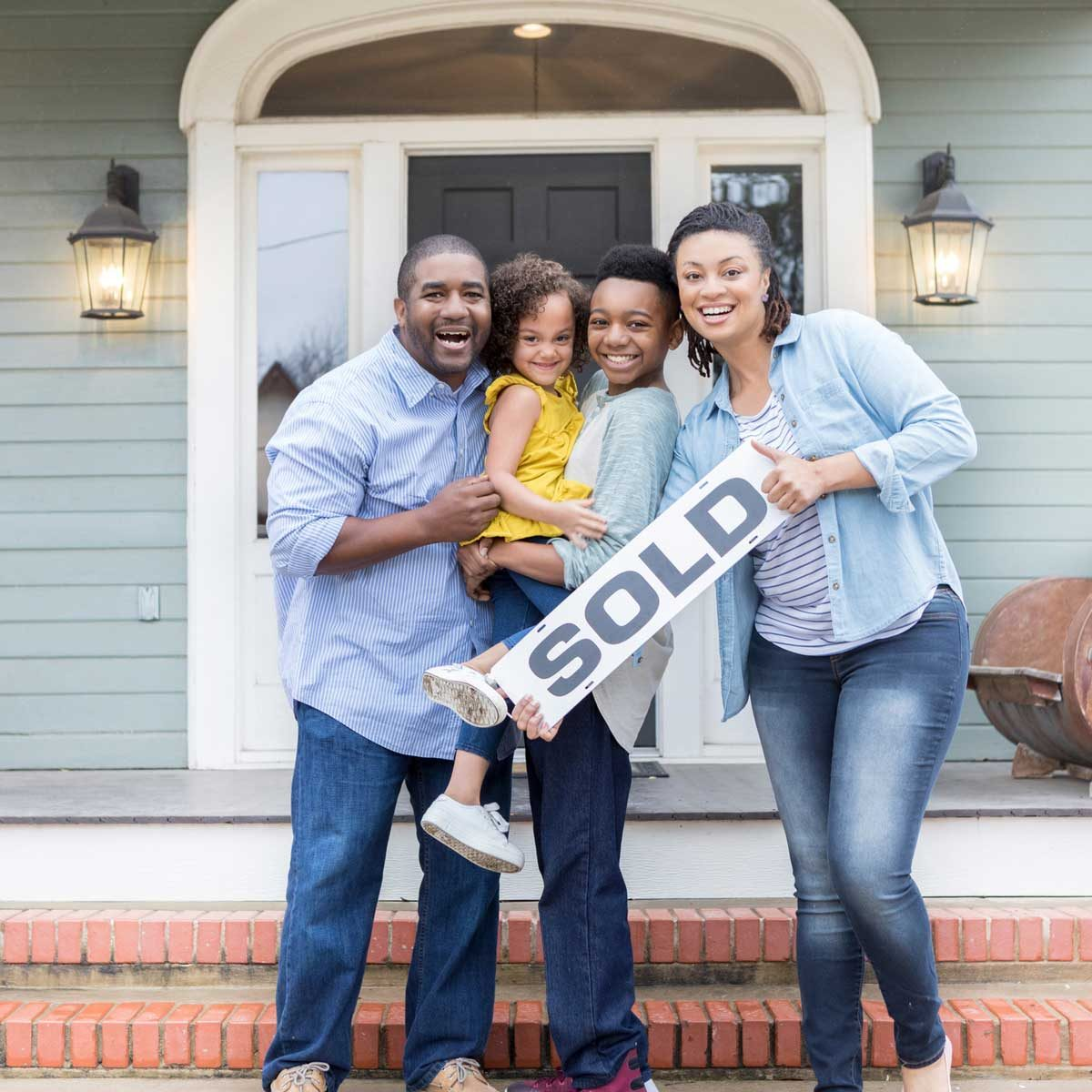 Family holding sold sign