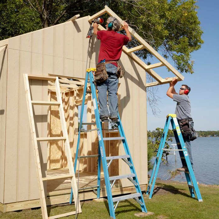 Men on ladders add an overhang to a shed