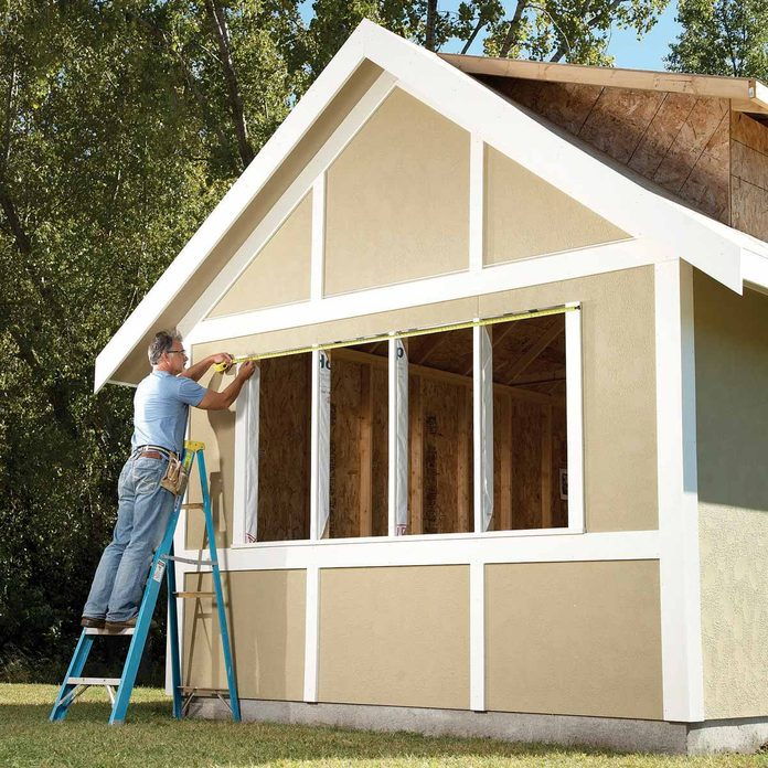 man stands on a ladder to measure shed