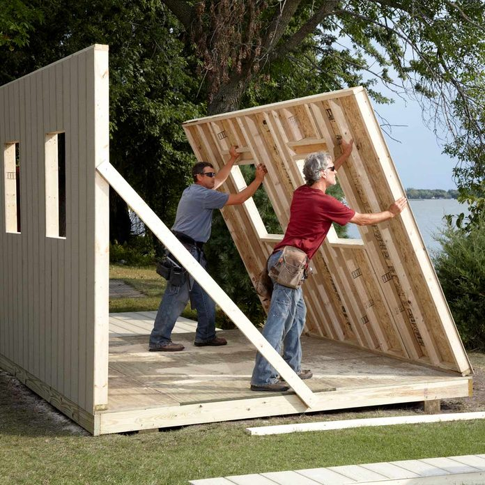 two men raise a shed wall overlook a lake