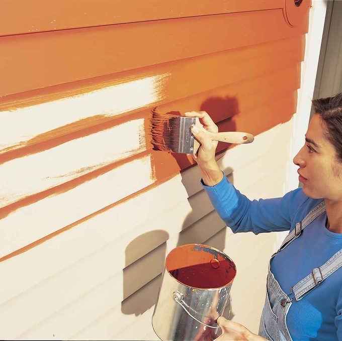 woman adds a coat of red-orange paint to a house