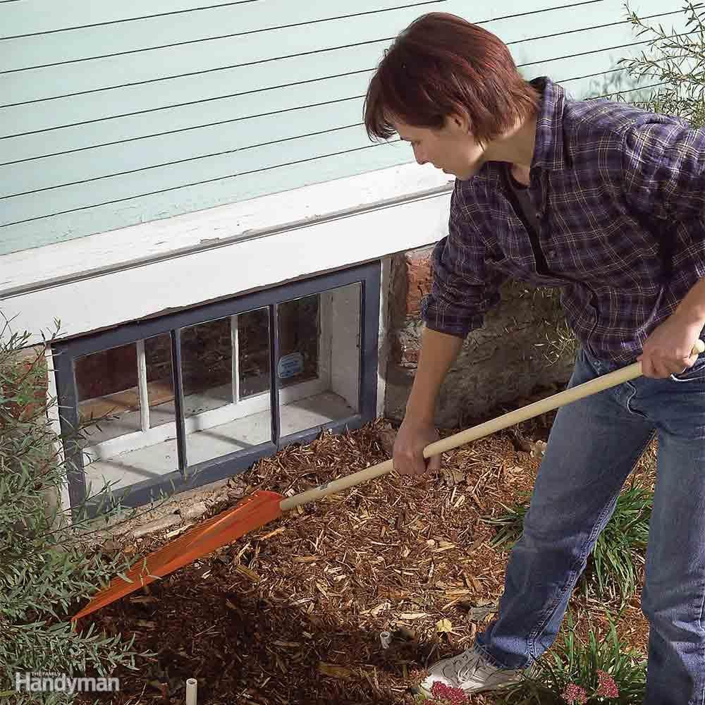 Woman rakes mulch away from egress window