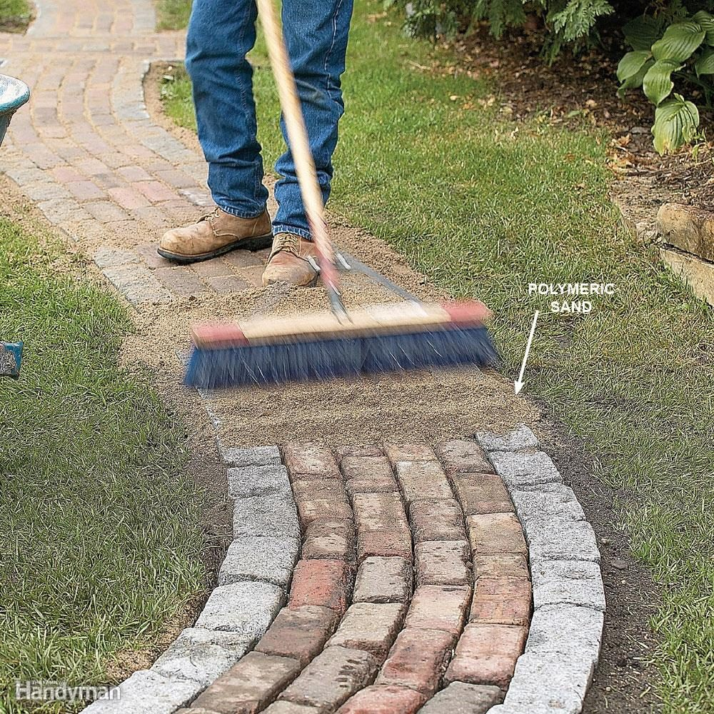 man sweeps sand along brick path