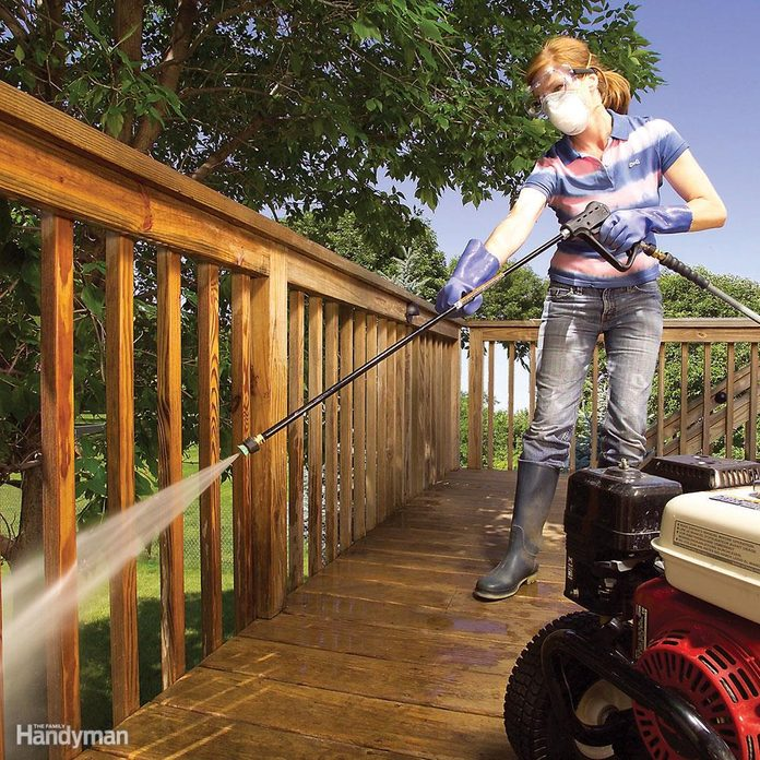 woman power washes a deck