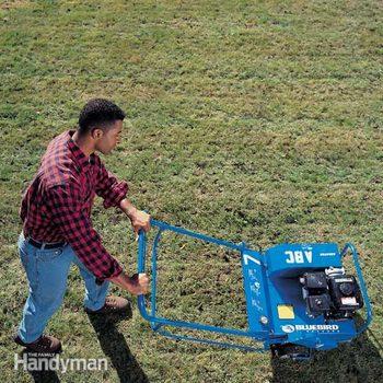 man walks behind an aerator on lawn