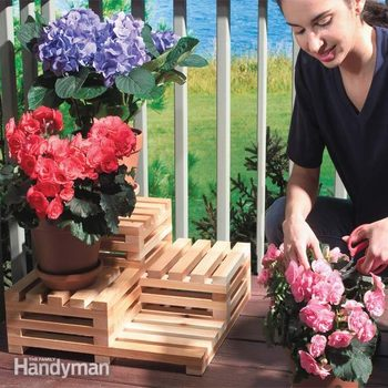 woman places flowers on a tiered plant stand