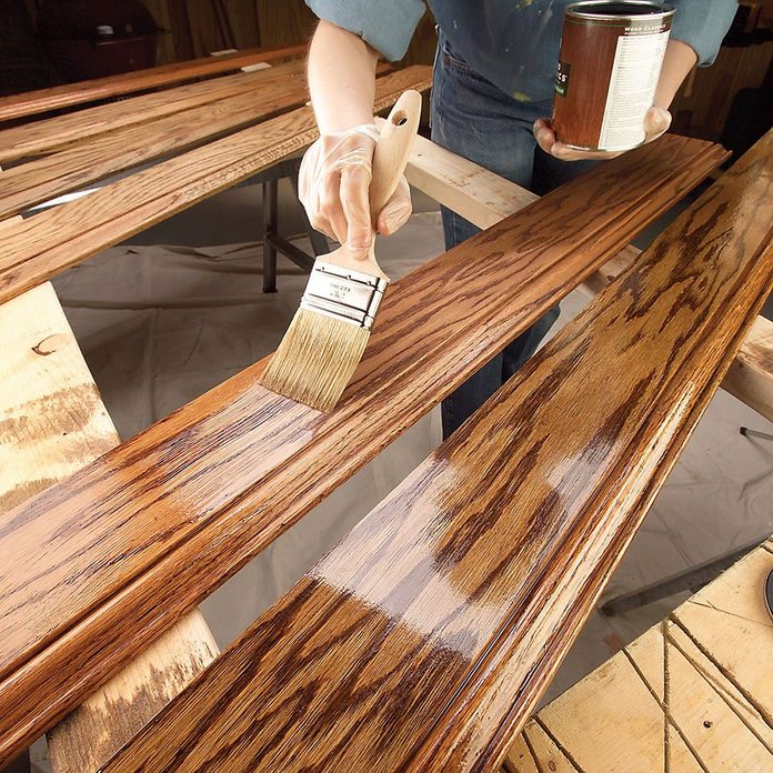 Brushing on a layer of finish onto a piece of trim | Construction Pro Tips