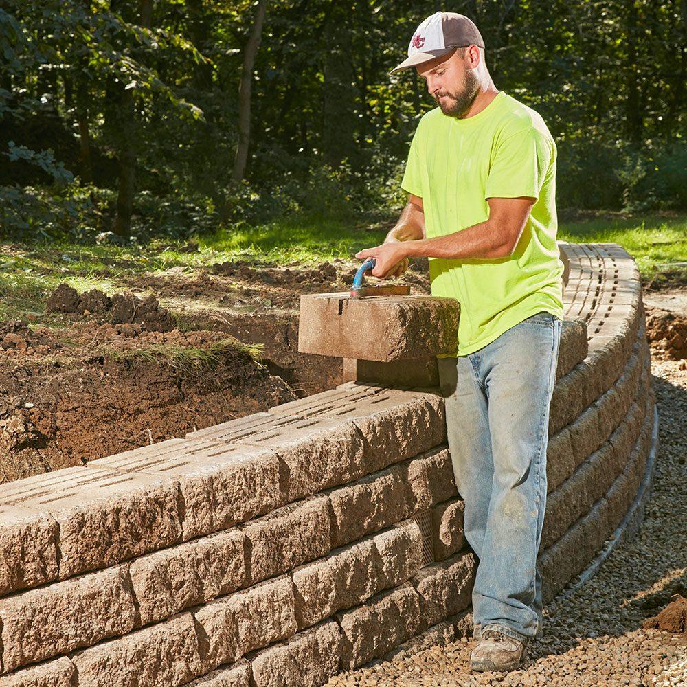 Man placing blocks onto a retaining wall | Construction Pro Tips