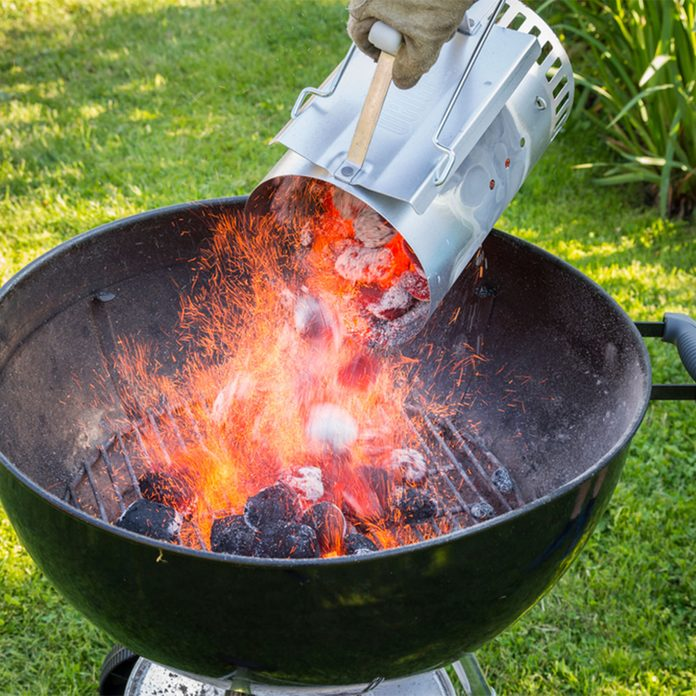 charcoal chimney pouring hot coals in grill