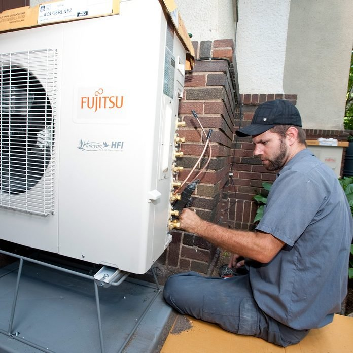 Man installing a mini-split   Construction Pro Tips