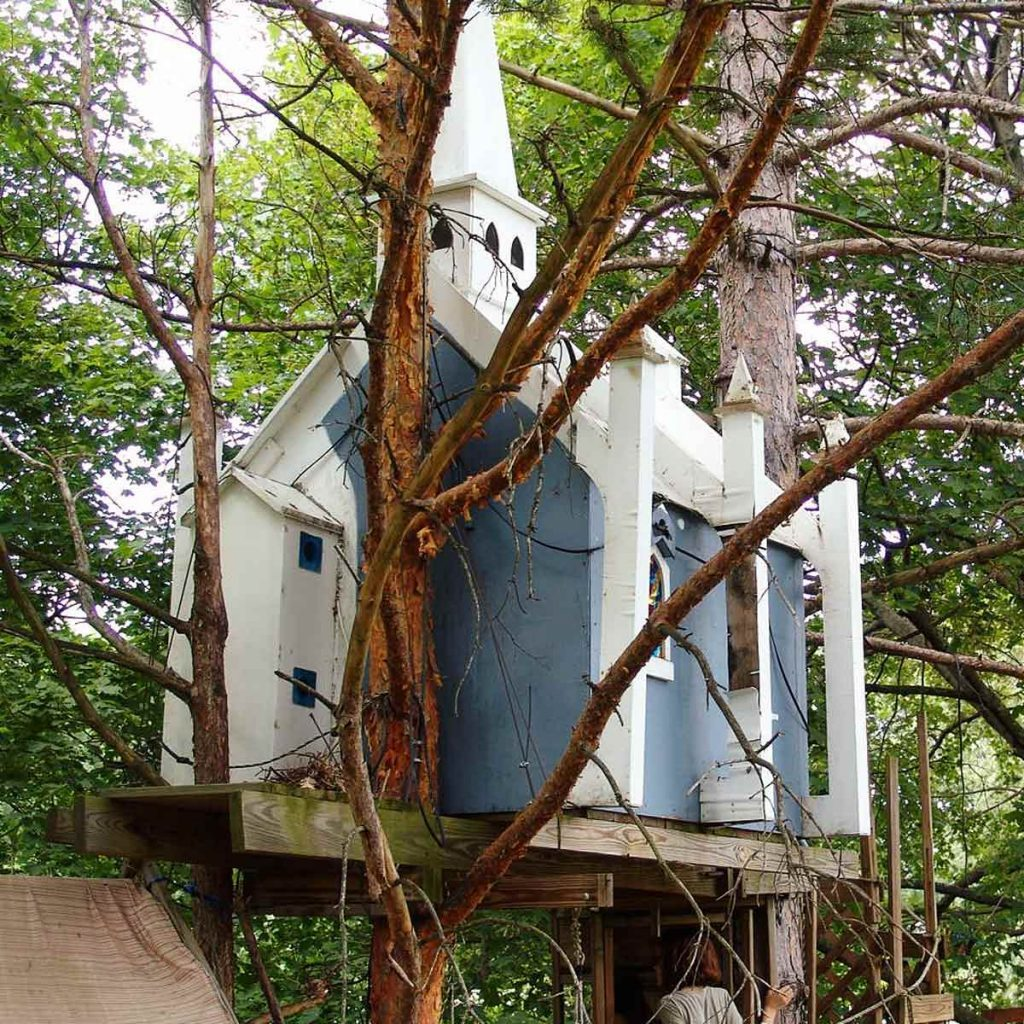 Blue and white treehouse that looks like a church
