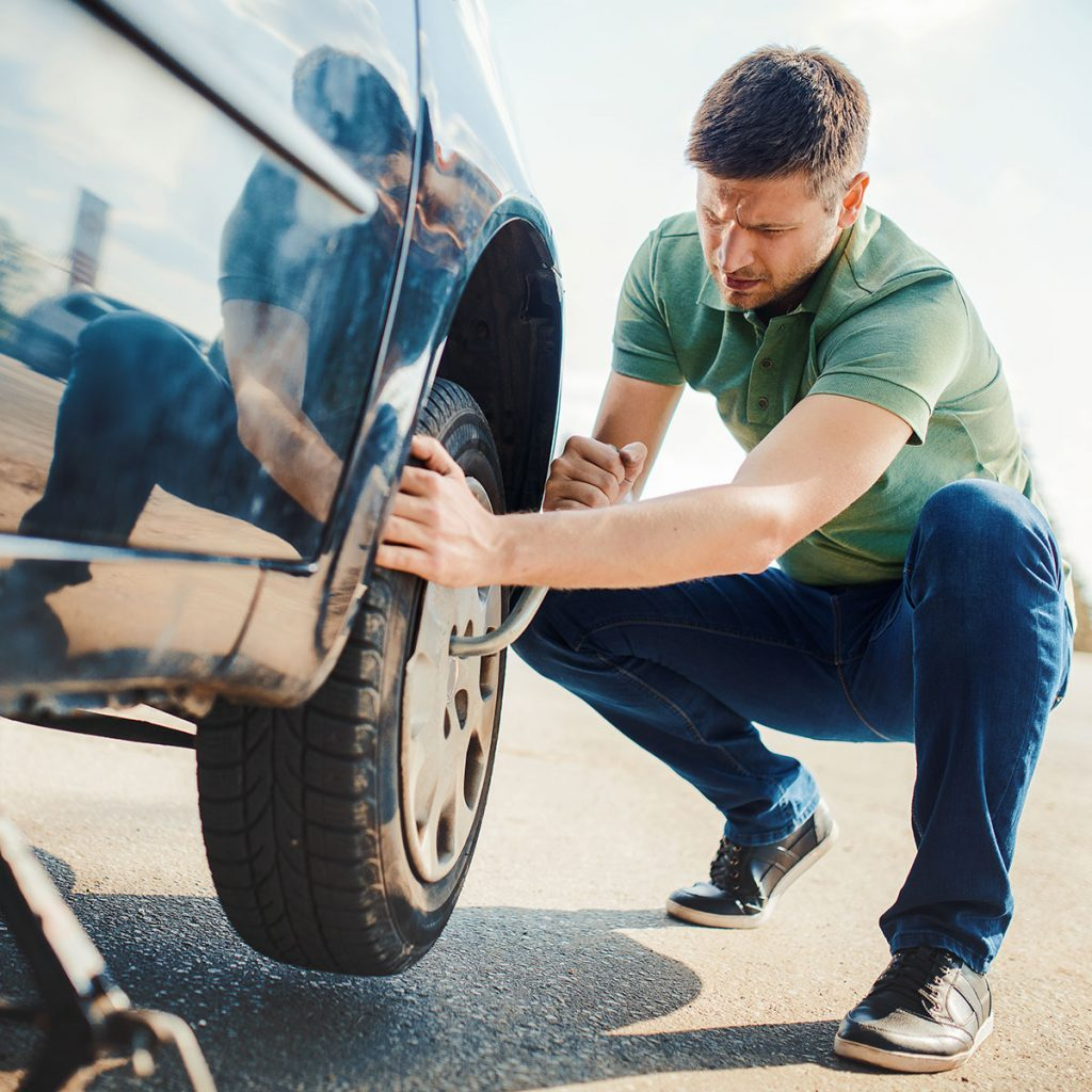 man changing a tire on the side of the road