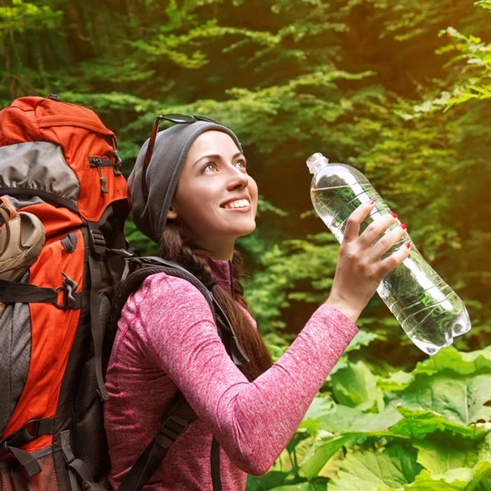 woman hiking and carrying water bottle hiking backpack