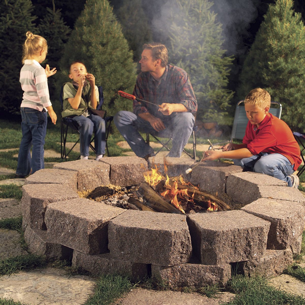 DIY fire pit fire ring backyard ideas Family roasting marshmellows around DIY firepit