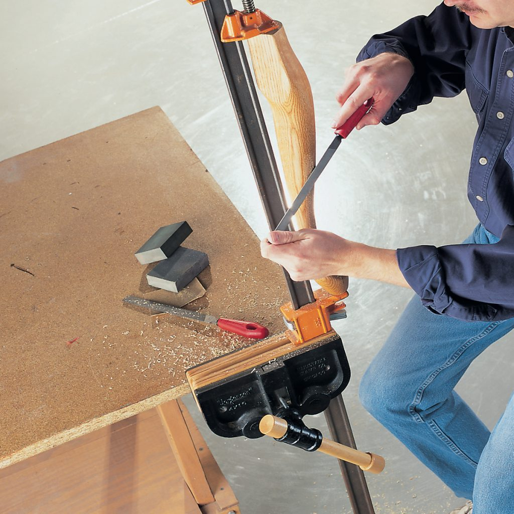 A man carving furniture in a clamp vise | Construction Pro Tips