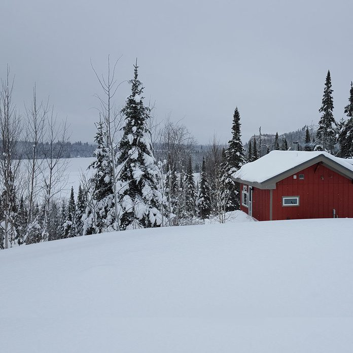 cabin covered in winter snow