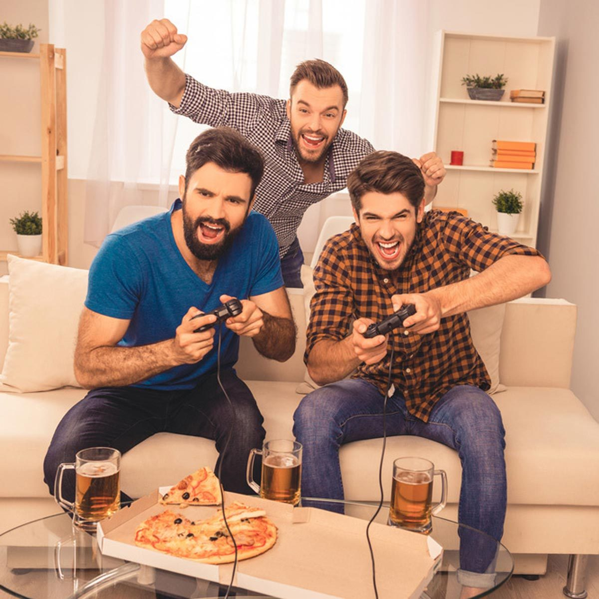 guys playing video games excited eating pizza and drinking beer friends