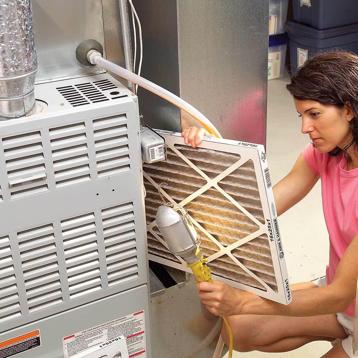 woman checks a furnace filter