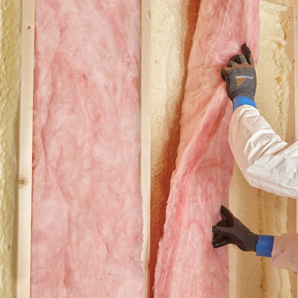 Laying fiberglass over spray foam | Construction Pro Tips