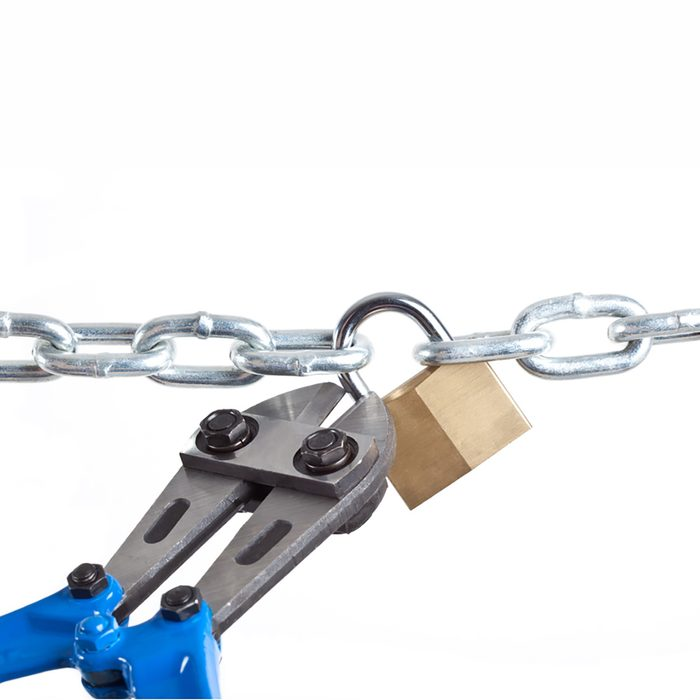 A bolt cutter snipping a padlock   Construction Pro Tips