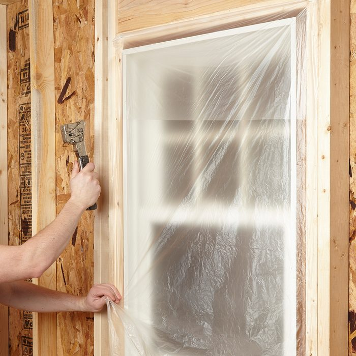 Covering windows with plastic to protect from overspray | Construction Pro Tips