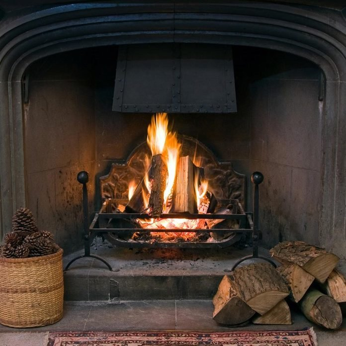 fire within a large stone arched fireplace, with pile of logs and basket of pine kernels