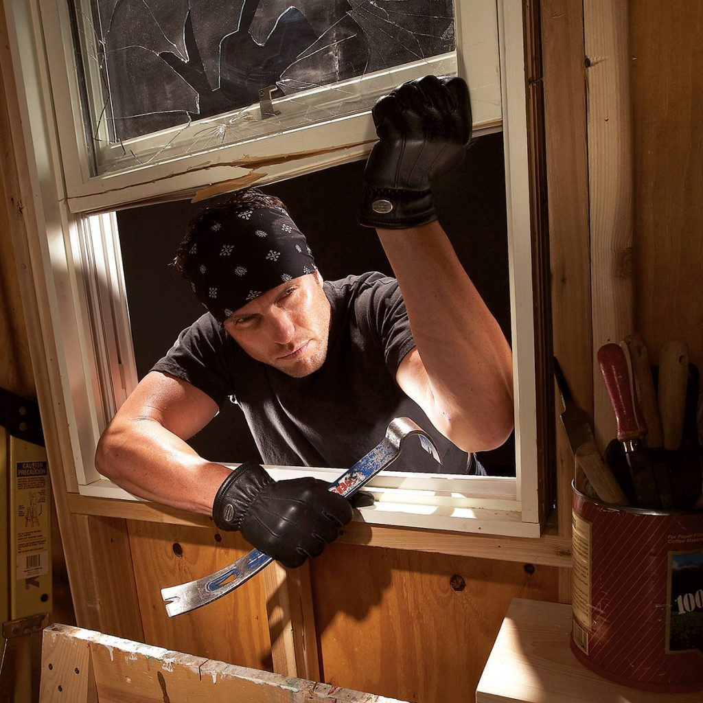 Man breaking into a garage through a window   Construction Pro Tips