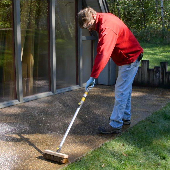 scrubbing concrete with stiff brush