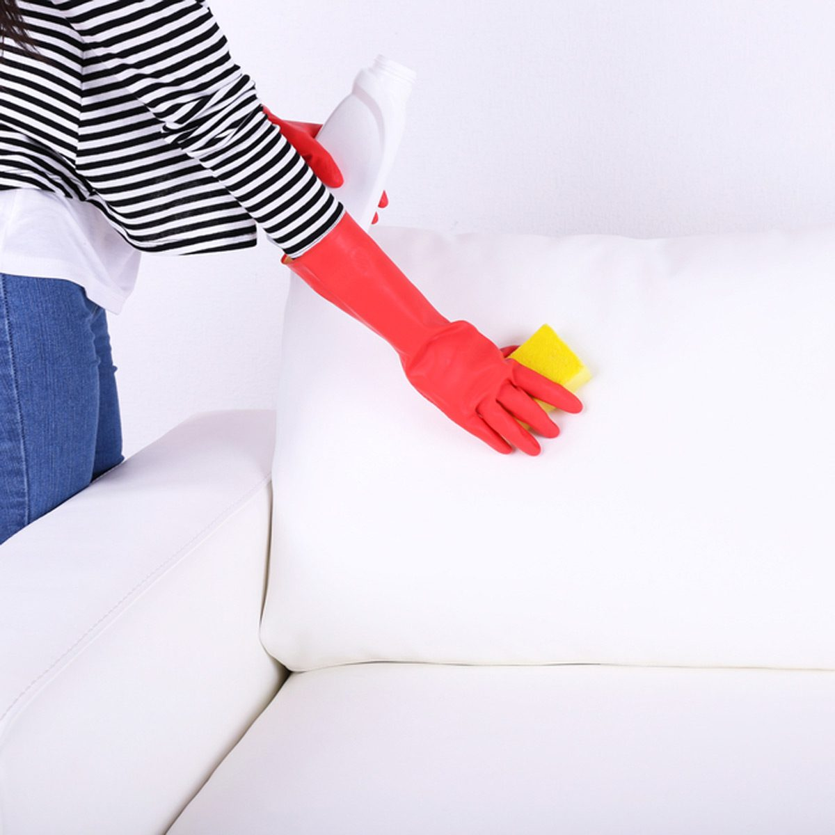 shutterstock_195200609 cleaning white couch furniture with natural cleaners rubber gloves