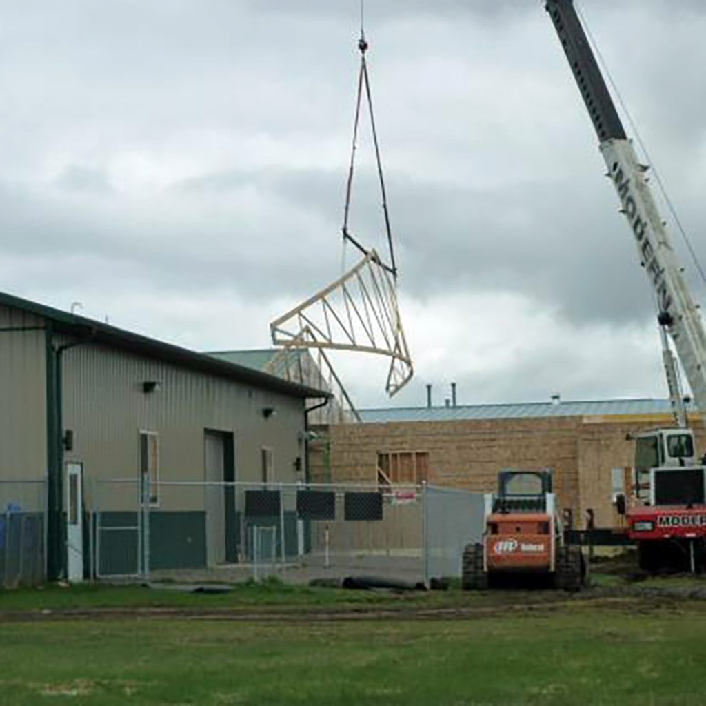 Hoisting Trusses over other buildings to put them in place | Construction Pro Tips