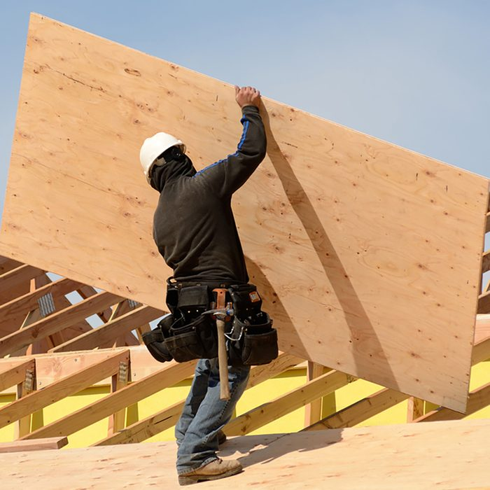 Placing plywood on top of assembled trusses | Construction Pro Tips