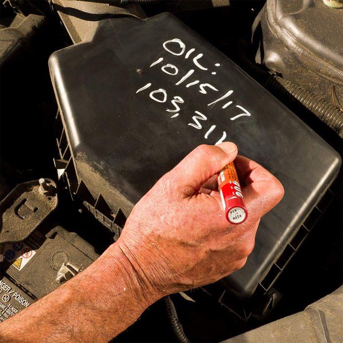 chalk marker under hood of car
