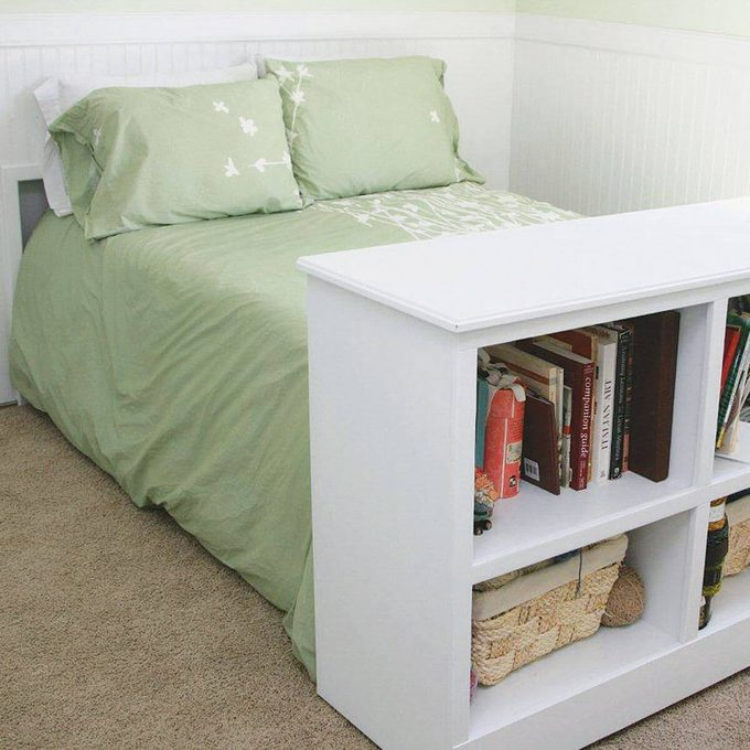 Pulled out bed on casters with bookshelf