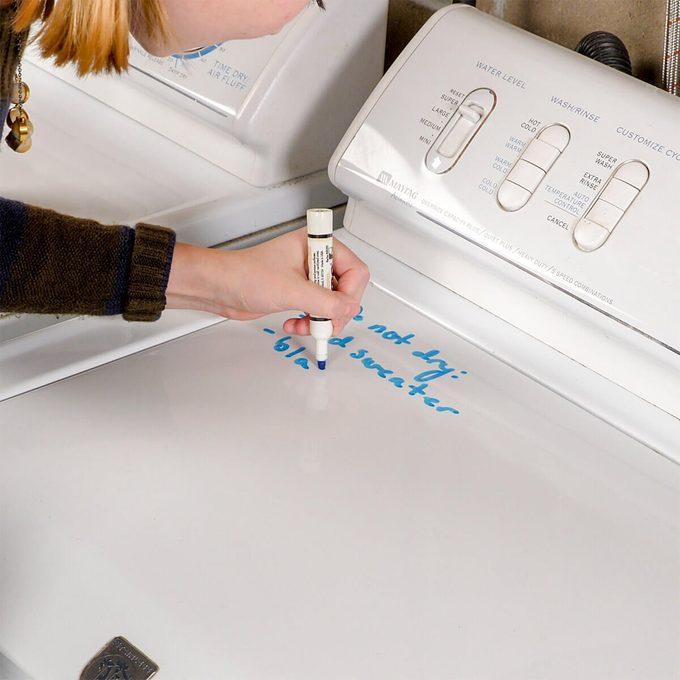 HH writing notes on washing machine laundry hack