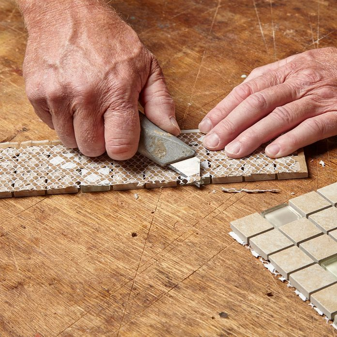 cutting off the extra strands of tile backer | Construction Pro Tip