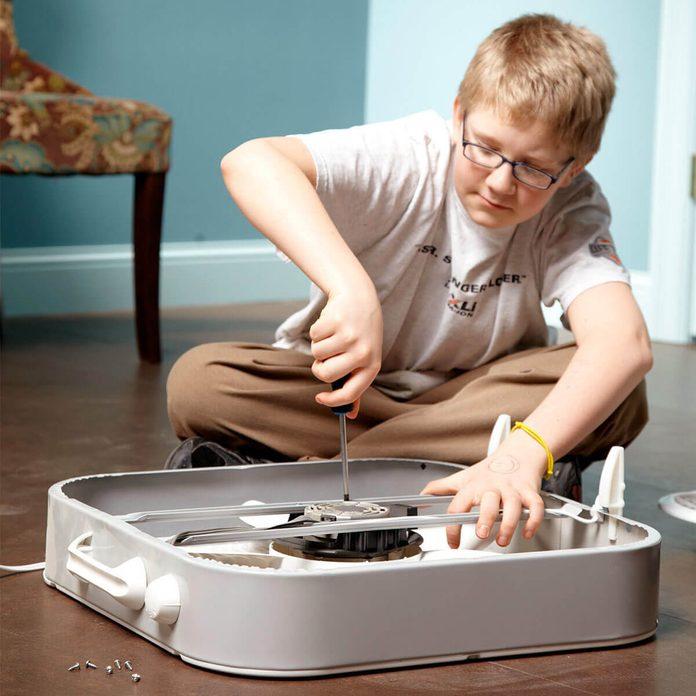 fh12jun_529_52_064 young boy repairing fixing box fan