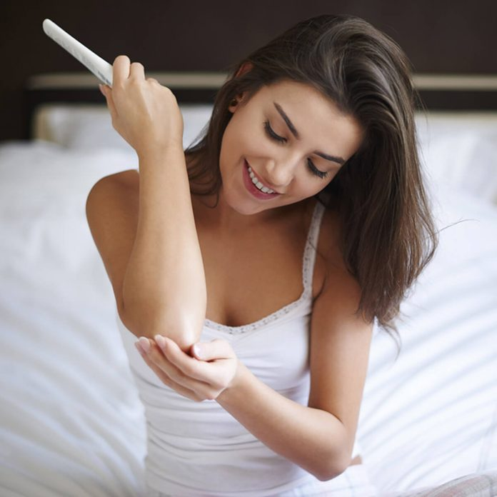 shutterstock_249497482 woman putting on lotion