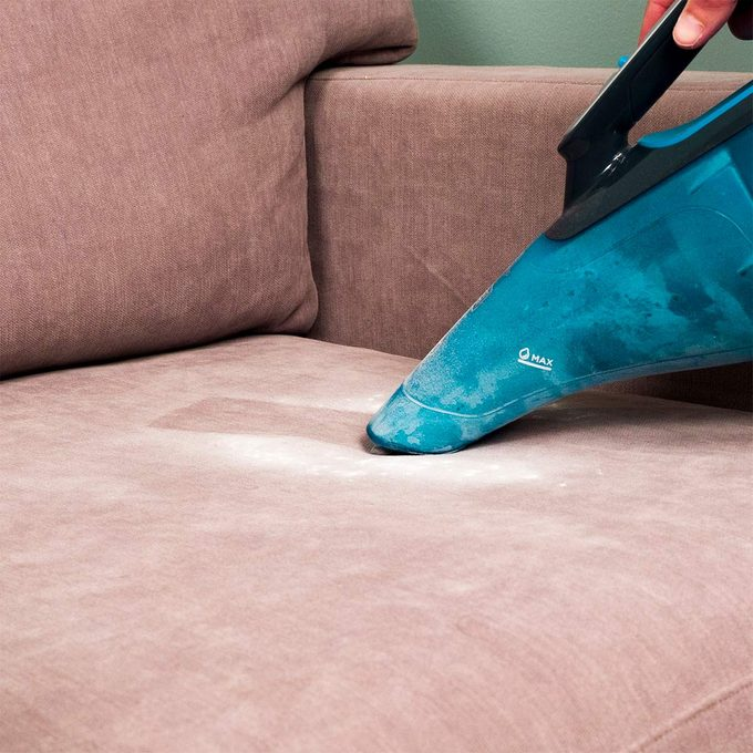 vacuuming up baking soda from upholstery