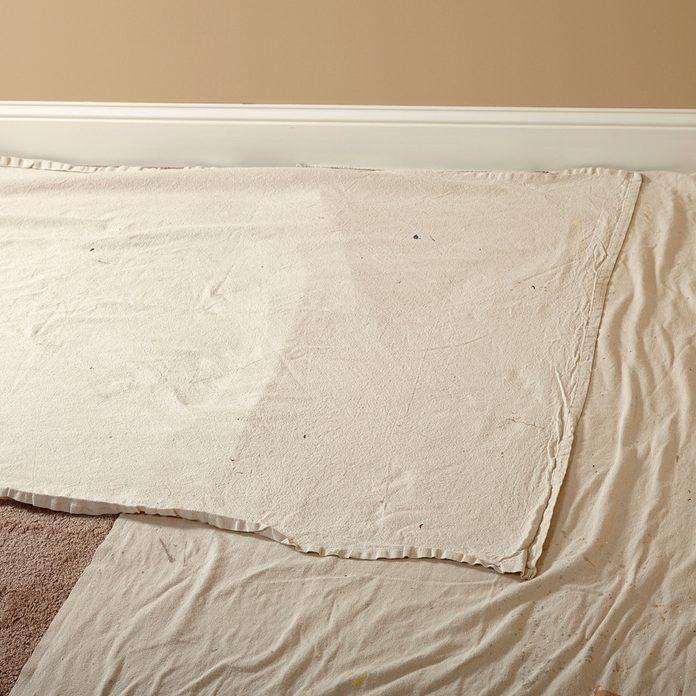 Laying down narrow drop cloths next the walls | Construction Pro Tips