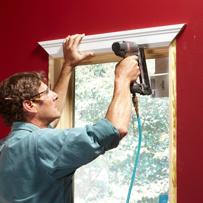 Stapling trim to the window for good spacing   Construction Pro Tips