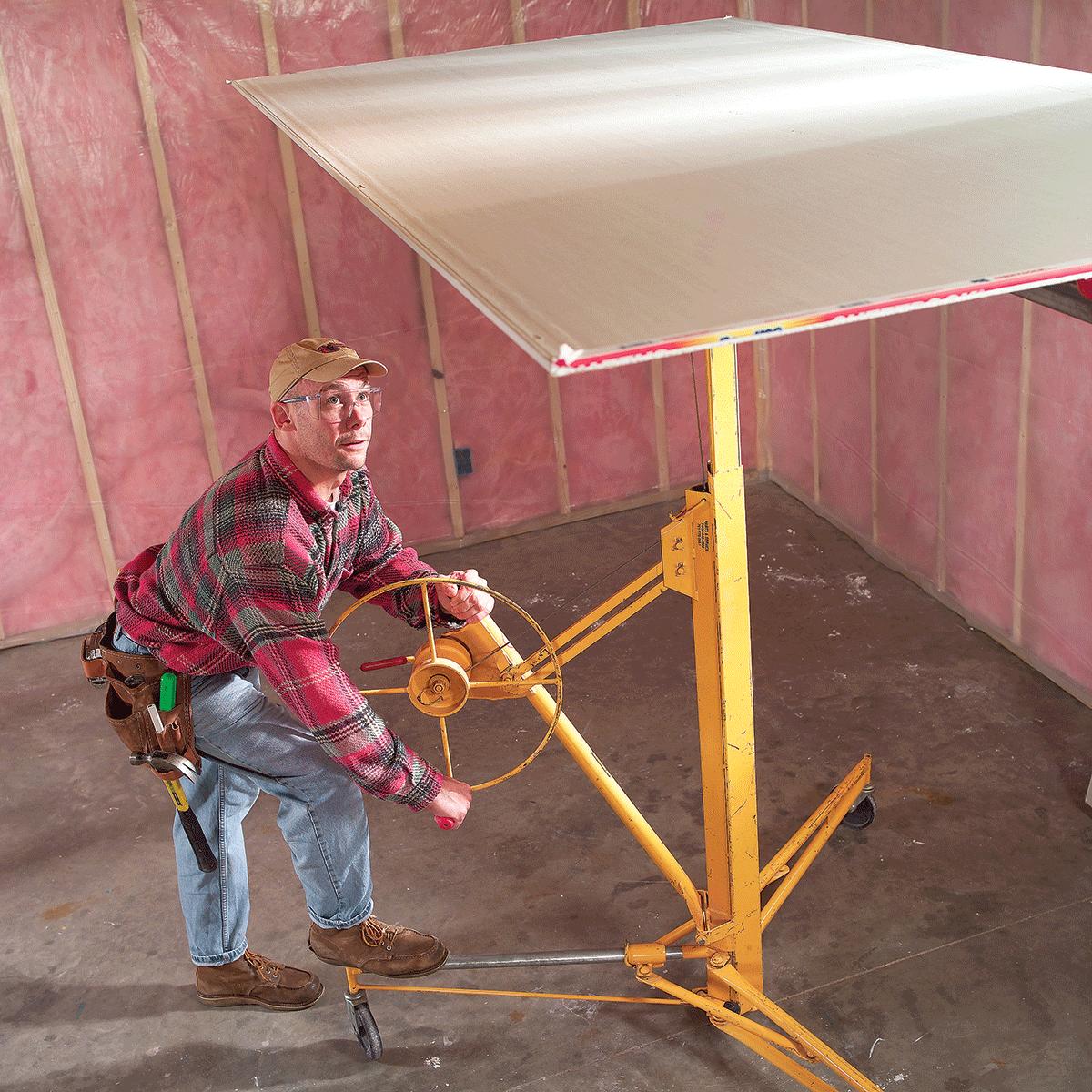 A man lifting drywall | Construction Pro Tips