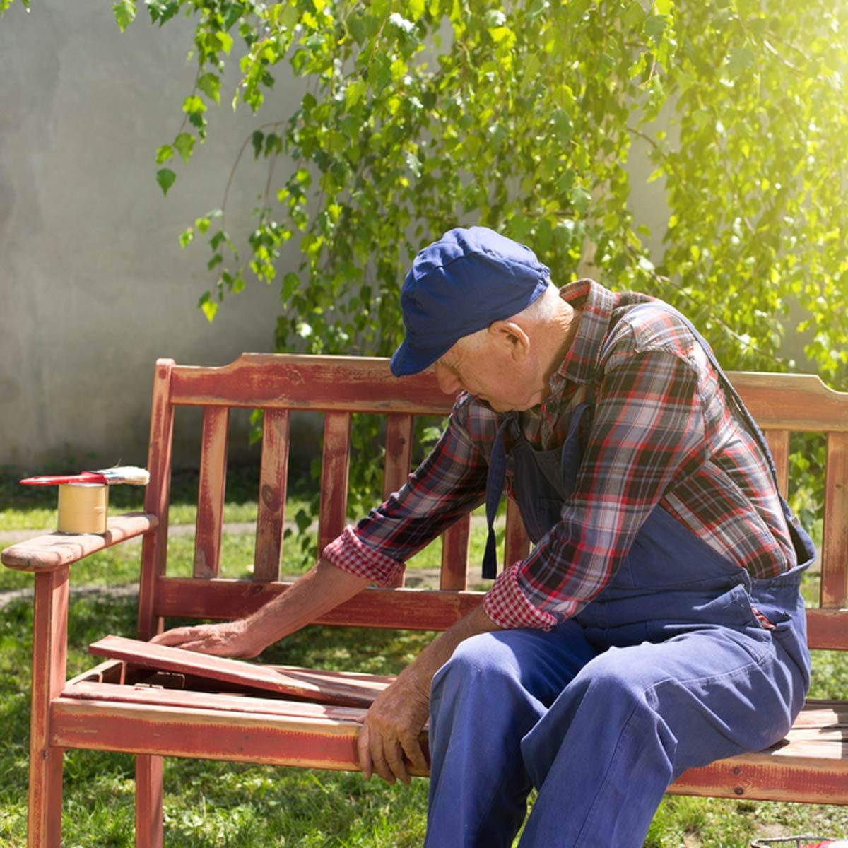Grandpa Man fixing a bench painting outdoor furniture